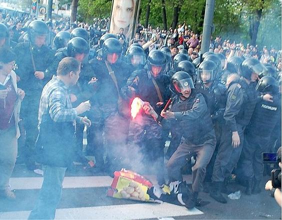 Полицейский бросает горящий фаер в протестующих (6 мая, Болотная площадь)
